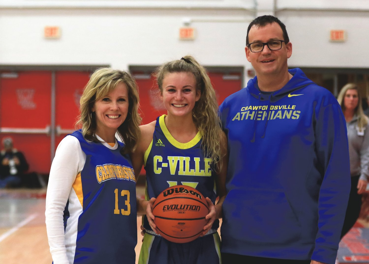 Crawfordsville's Lauren Kellerman stands alongside her parents, Kevin and Holly Kellerman, with a game ball to celebrate her 1,000th point.