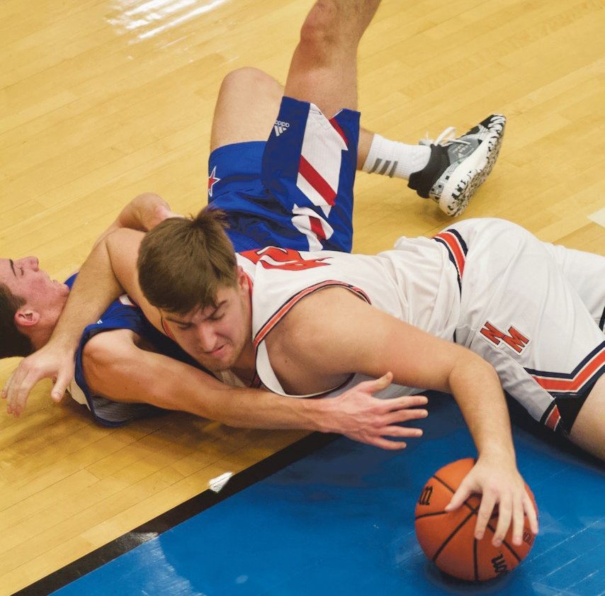 North Montgomery's Jack Thompson fights for a loose ball. The senior scored 10 points in the Chargers 50-49 loss to Western Boone.