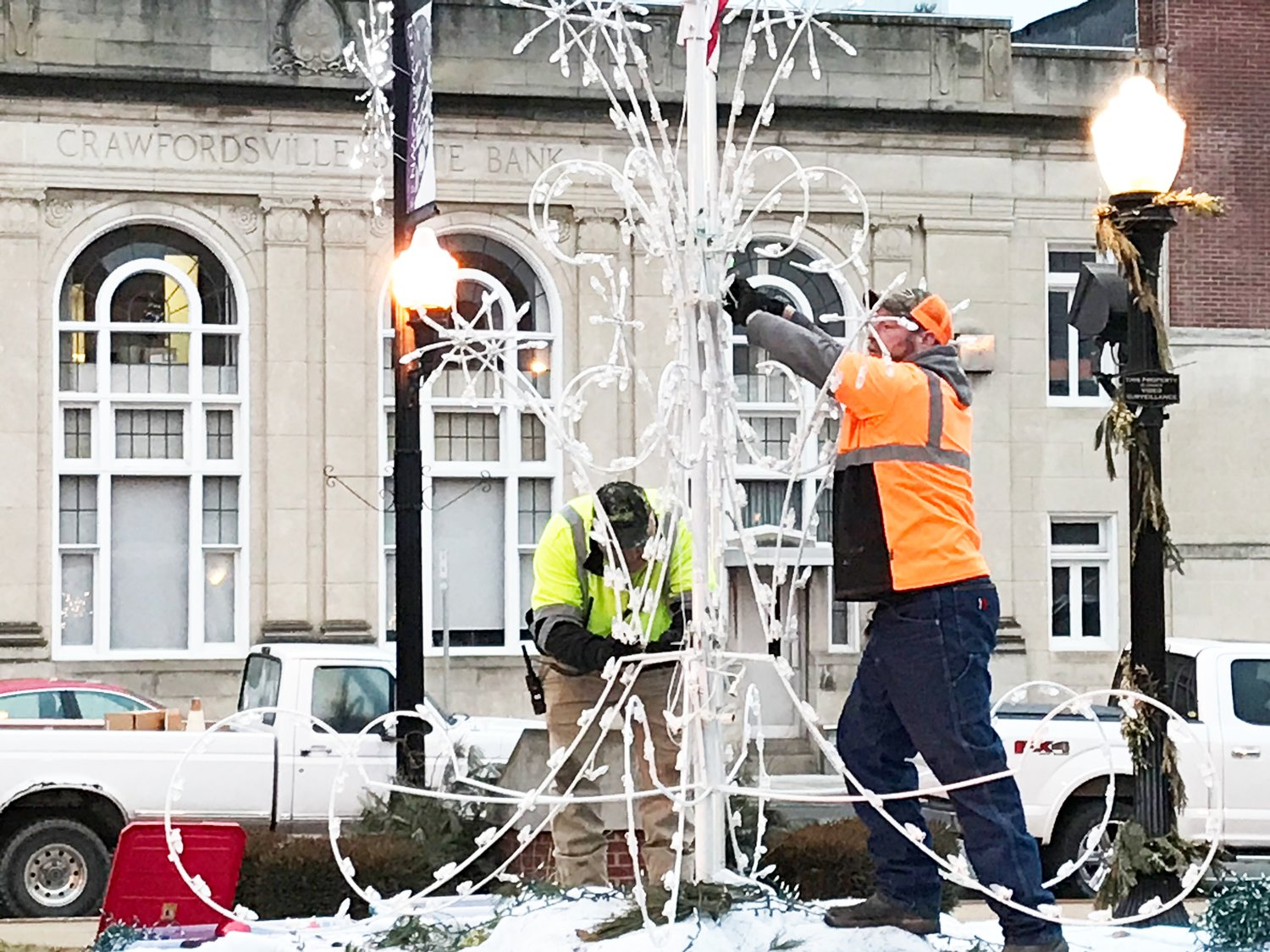Crawfordsville Street Department employees take down holiday decorations Tuesday at Pike Place.