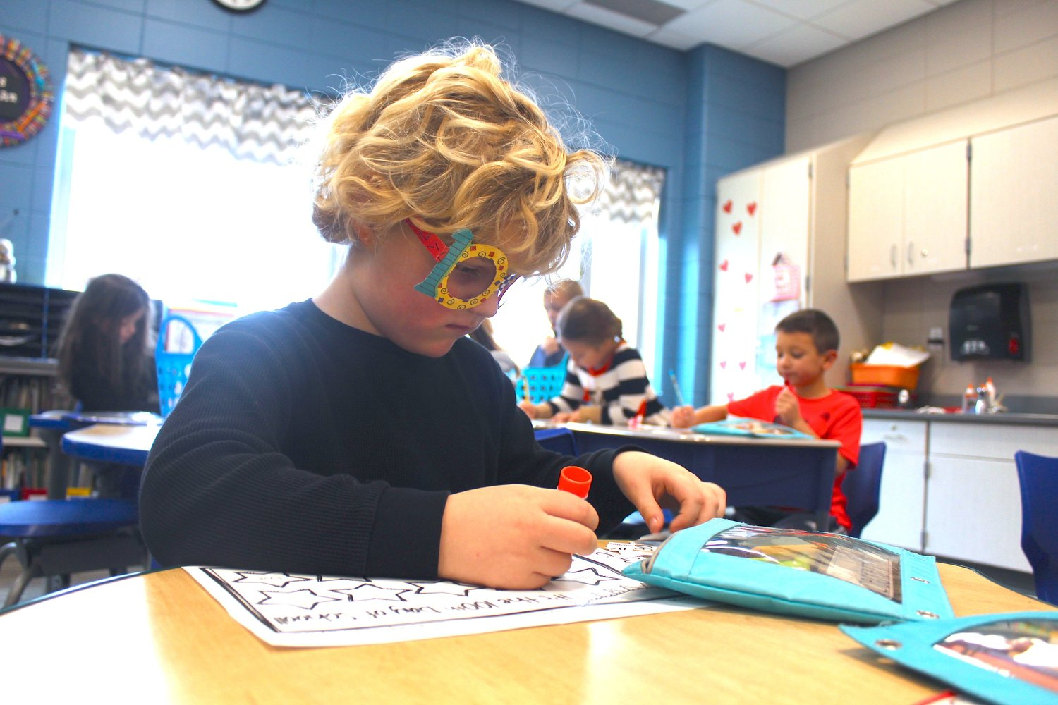Beckett Bonebrake pastes stars at another 100th Day station Friday at Sommer Elementary.