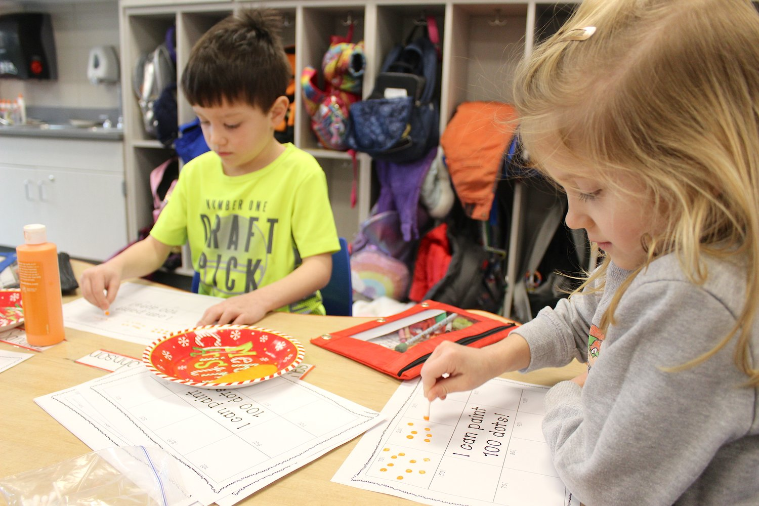 Painting 100 dots, 10 at a time, are Alex Johnson and Caitlin Jeffries during their 100th day of school.