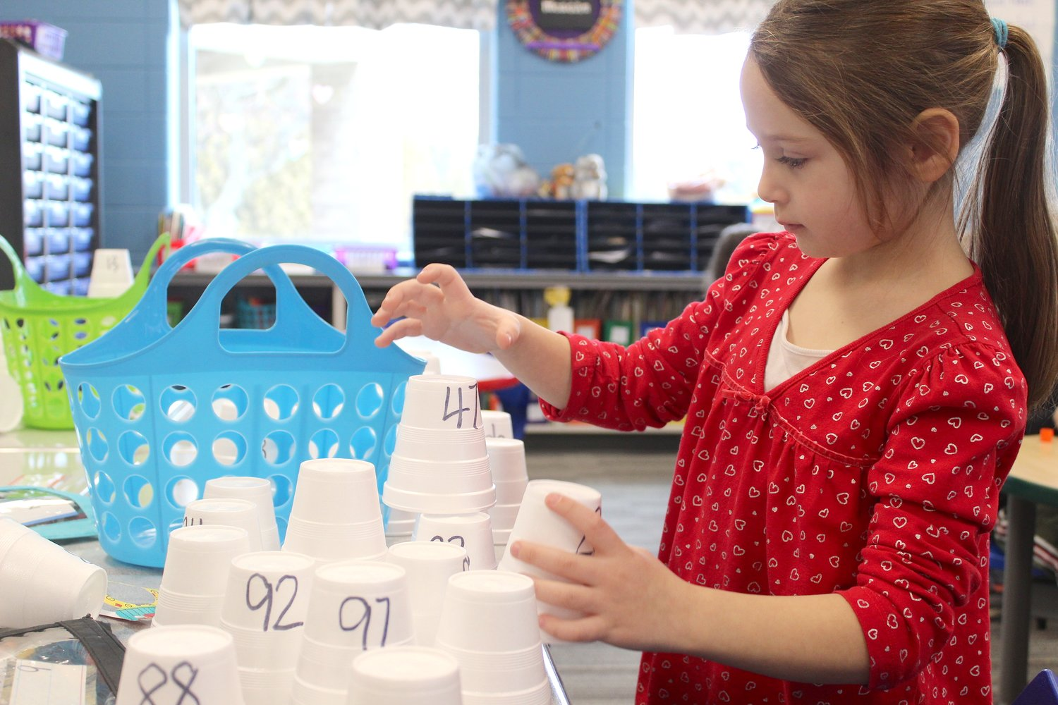 Kindergarten student Arya Steward builds a pyramid of cups with numbers one through 100 Friday at Sommer Elementary.