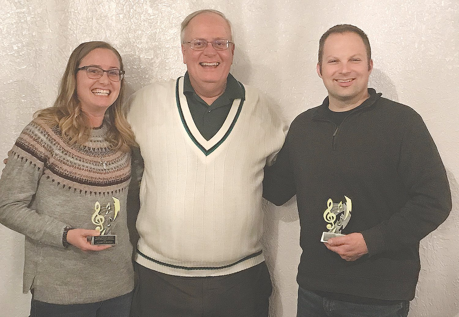 Elizabeth Newnum, left, and Andrew Simpkins, right, pose with Mark Eutsler after being honored with the 2019 Moffit Music Education Award.