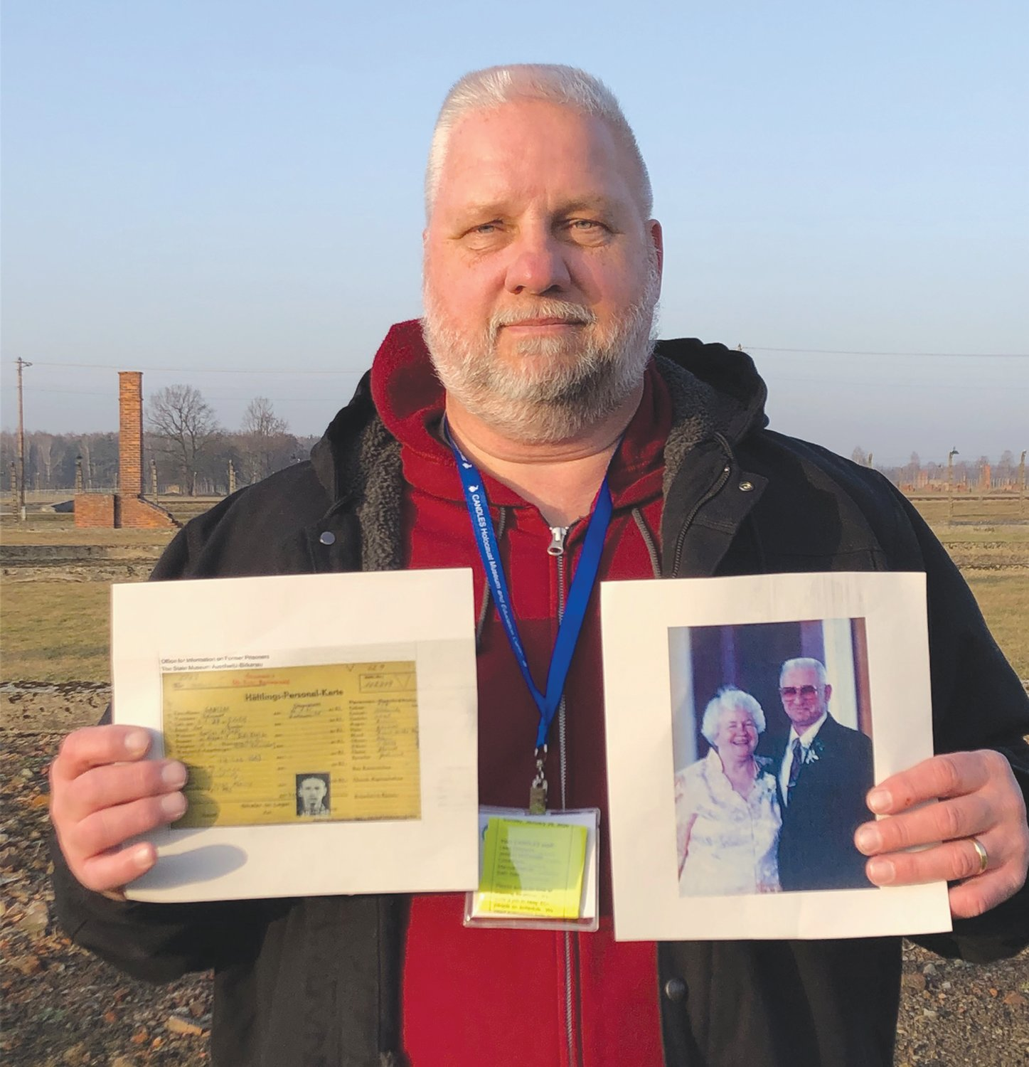 Tony Gonczarow, a Southmont High School teacher, holds his father's record and a photograph of his parents during the 75th anniversary of the liberation of Auschwitz on Monday.