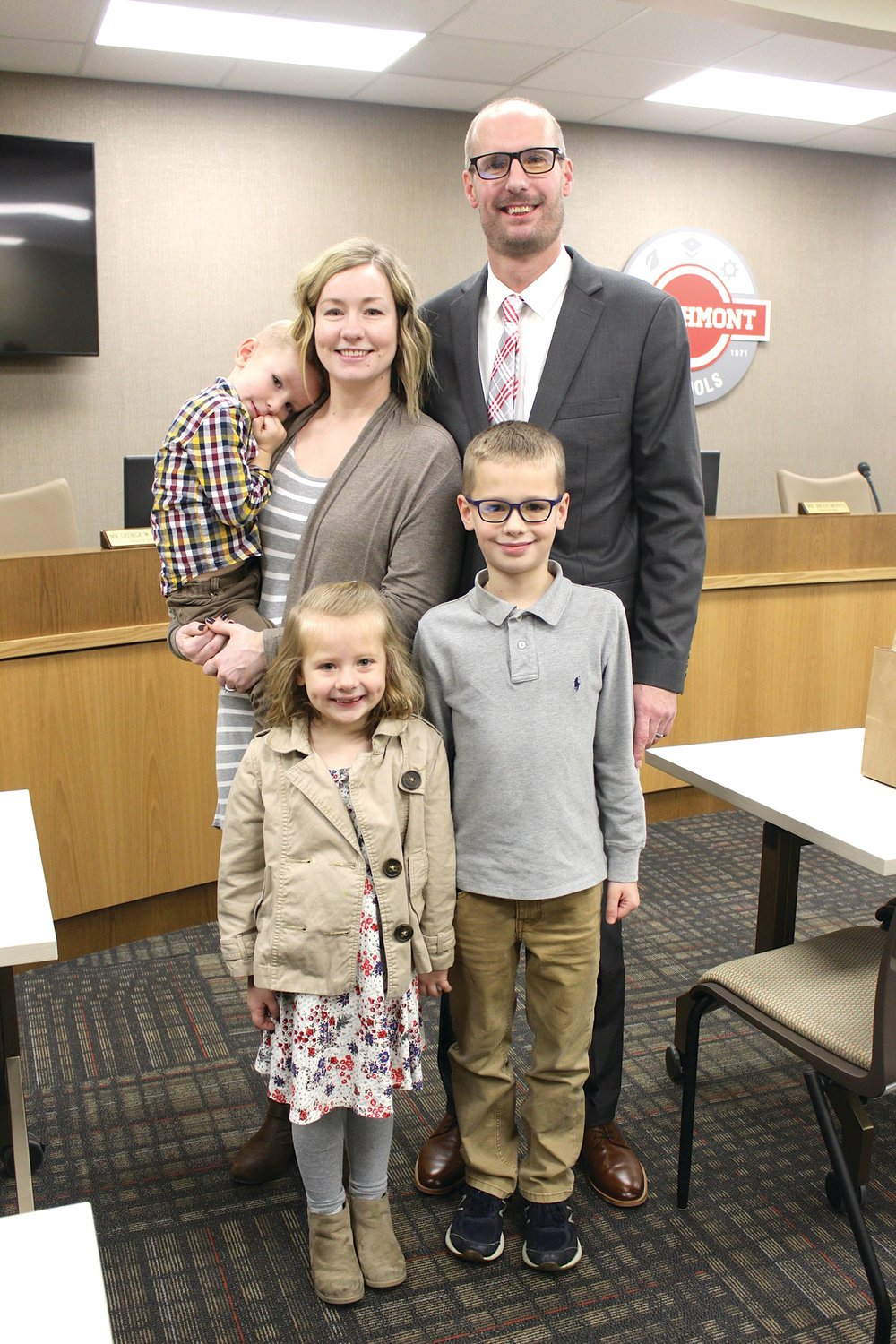 Jesse Burgess, newly hired as principal at Southmont High School, stands tall with his after receiving approval from the Southmont school board Monday. Burgess was accompanied by his family Monday, including his wife Jenna, his six-year-old daughter Cora and sons Caleb, standing, and Knox.