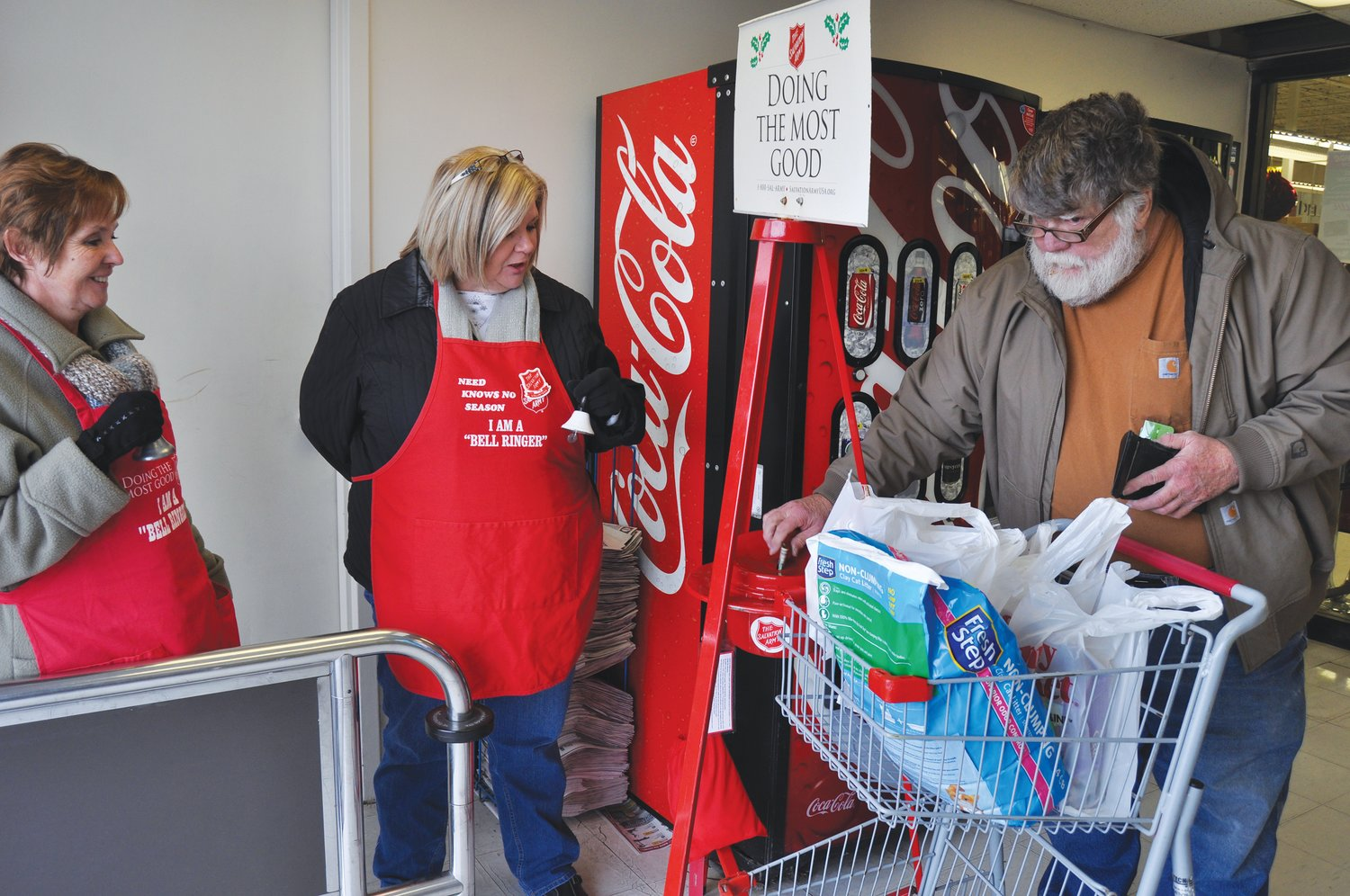 Jasper Cox puts cash in the Salvation Army Red Kettle at County Market, as bell ringers Faye Cooksey and Sandy Webb look on during the 2017 kettle campaign.