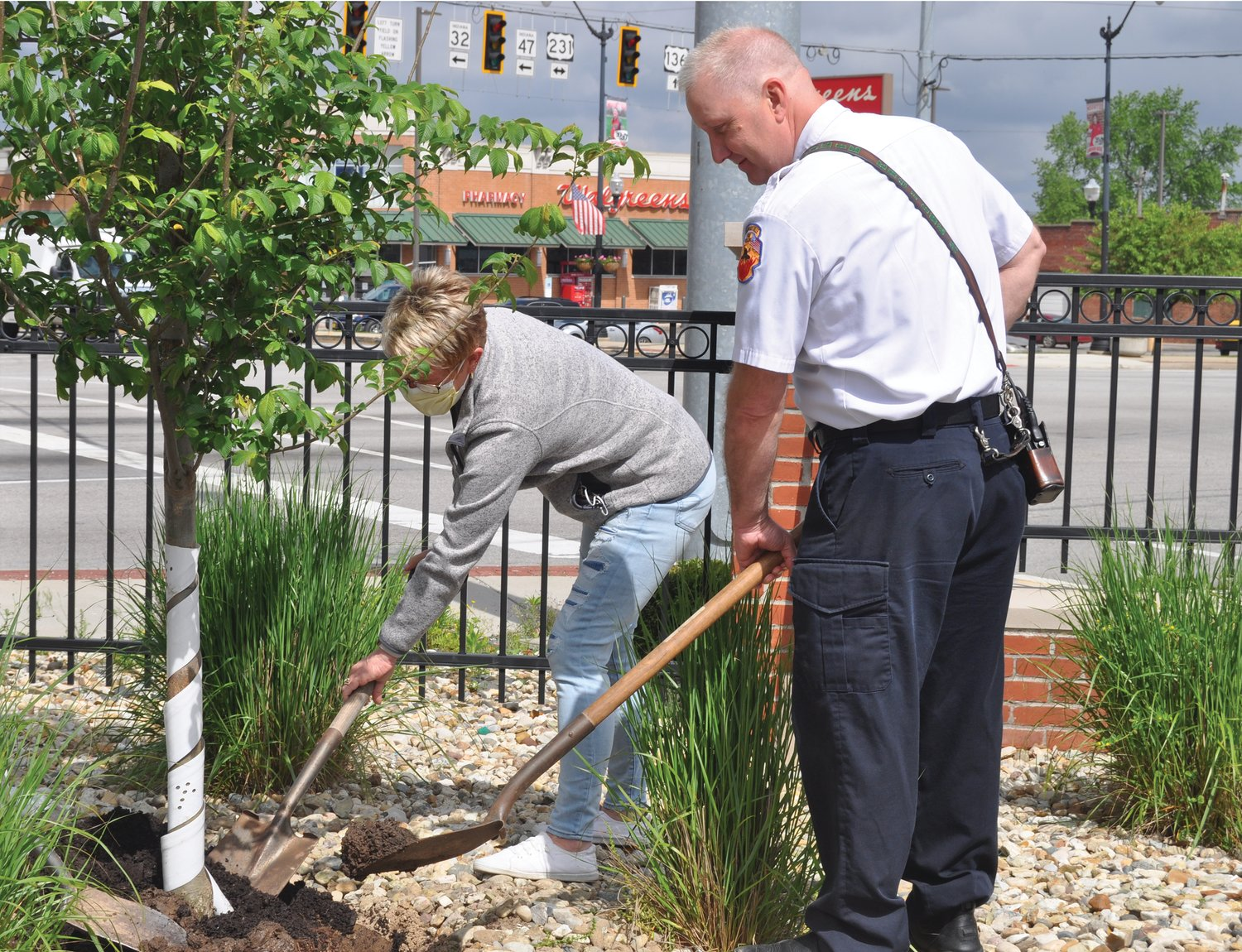 Amber Reed, left, Montgomery County Health Department administrator, and Scott Busenbark, Crawfordsville fire chief, shovel dirt around a Patriot Elm Tree Friday in the Montgomery County Courthouse parking lot. The tree was dedicated to front-line workers in the COVID-19 pandemic by Crawfordsville Main Street.