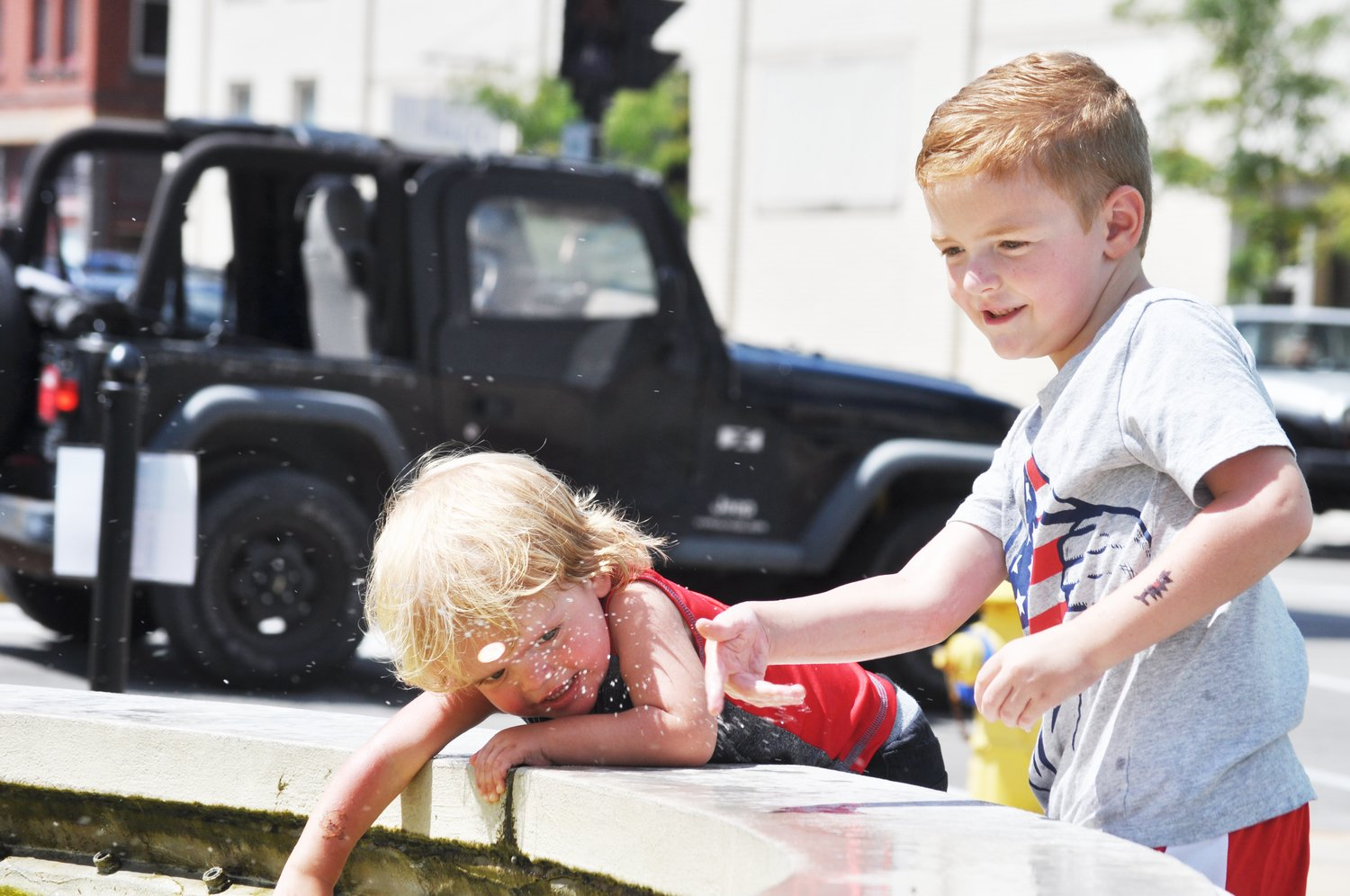 Aden Beck, 6, right, and his brother, Mathis, 2, play in the fountain at Marie Canine Plaza during Lunch on the Plaza 2.0 Friday.