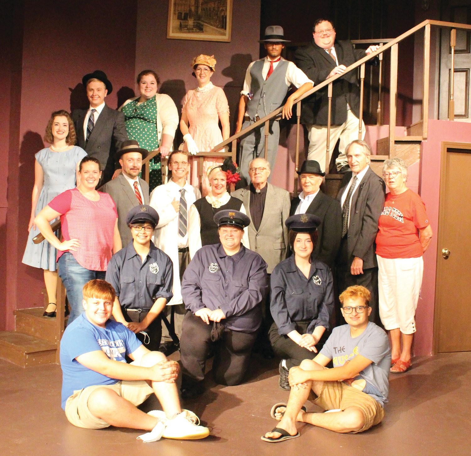 Members of the cast for Arsenic and Old Lace, are, from left, front row, Harmon Hann and Ross Tunin (both techs); second row, Alecsandra Baldwin (Officer Brophy), Lora Burris (Officer O'Hara), Nicole Hays (Officer Klein); third row, Katie Melvin (director), Adrian Burris (Mr. Gibbs), Alan Hobson (Dr. Einstein), Carol Homann (Mrs. Harper), Kurt Homann (Rev Dr. Harper), Kenn Clark (Mr. Witherspoon), Keith Strain (Lt. Rooney), Betsy Strain (producer); and on the stairs, Michaela Semak (Elaine Harper), Mike Melvin (Mortimer Brewster), Mary Taylor (Abby Brewster), Cheri Clark (Martha Brewster), Isaac Bacon (Jonathan Brewster) and Dan Martin (Teddy Brewster).
