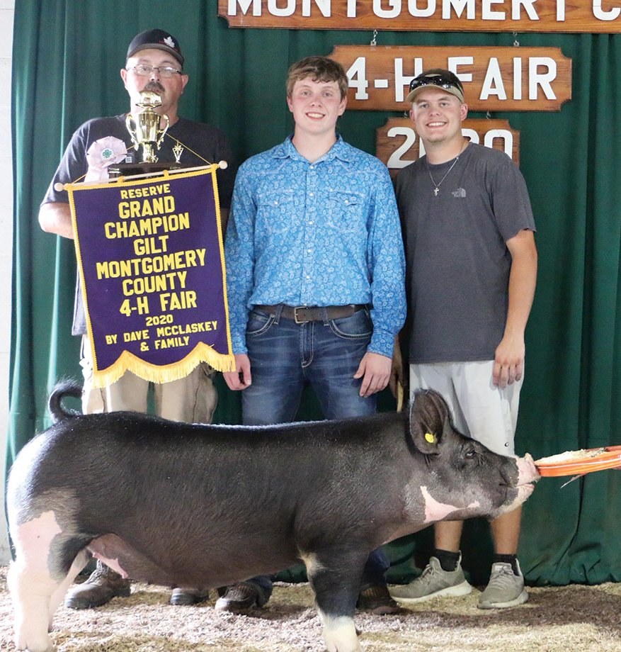 Don Martin, from left, Collin Martin and Brinton Sieferman pose for a quick photo in front of the 2020 Montgomery County 4-H Fair backdrop following an award presentation in which Collin received Reserve Grand Champion Gilt for his animal.