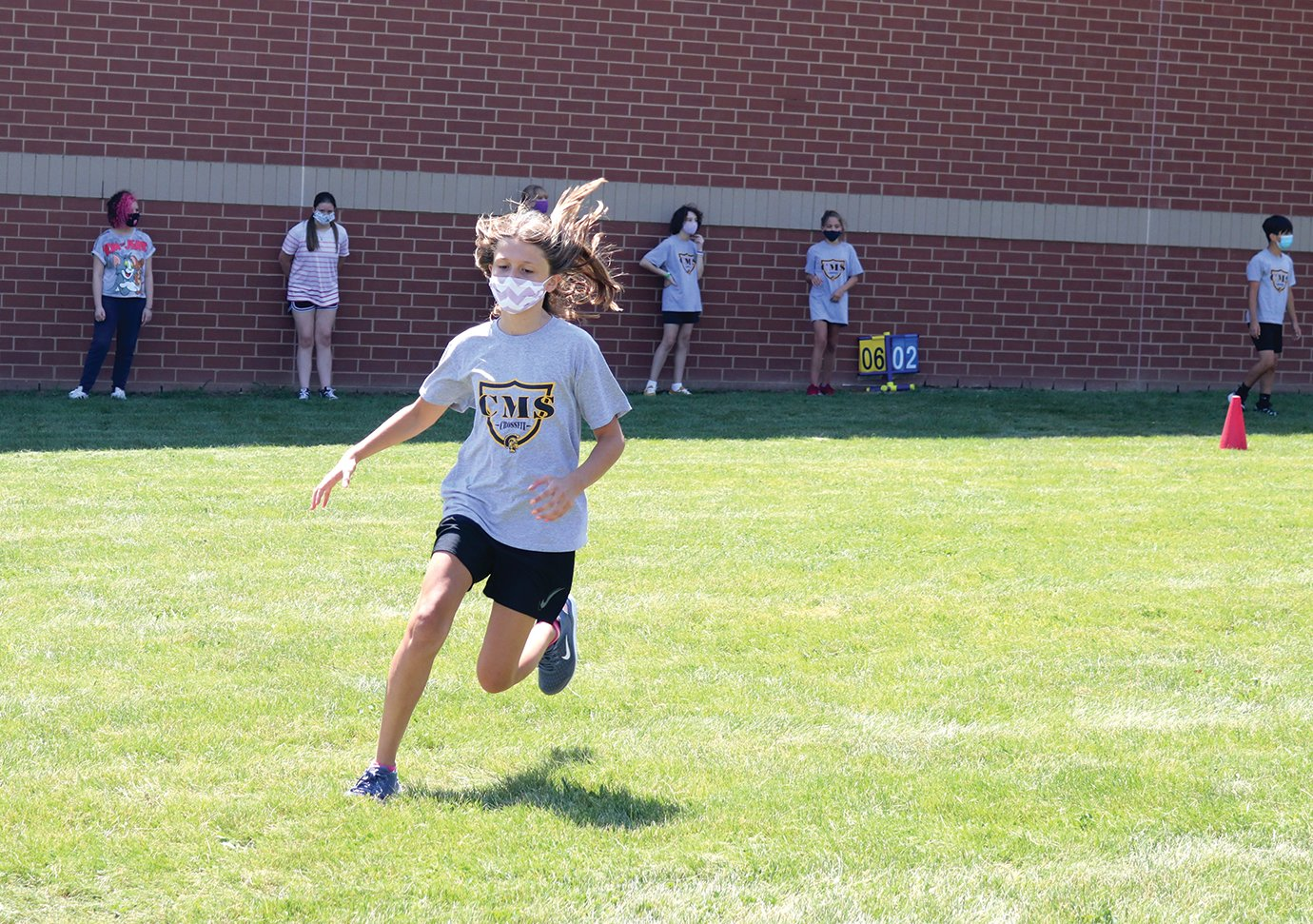 "Sixth-grade student Sydney Elizonzo heads to first base Tuesday during a cardio softball game at Crawfordsville Middle School in which students play timed innings instead of counting ""outs."""