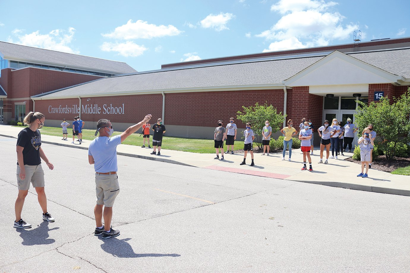 Physical education teachers Amanda Elizonzo and Andy Craig, left, instruct a seventh-grade class to warm up for a game of cardio softball by walking around the south parking lot at Crawfordsville Middle School. Student would run and walk for 20 seconds at a time to get loose and enjoy an outdoor break.