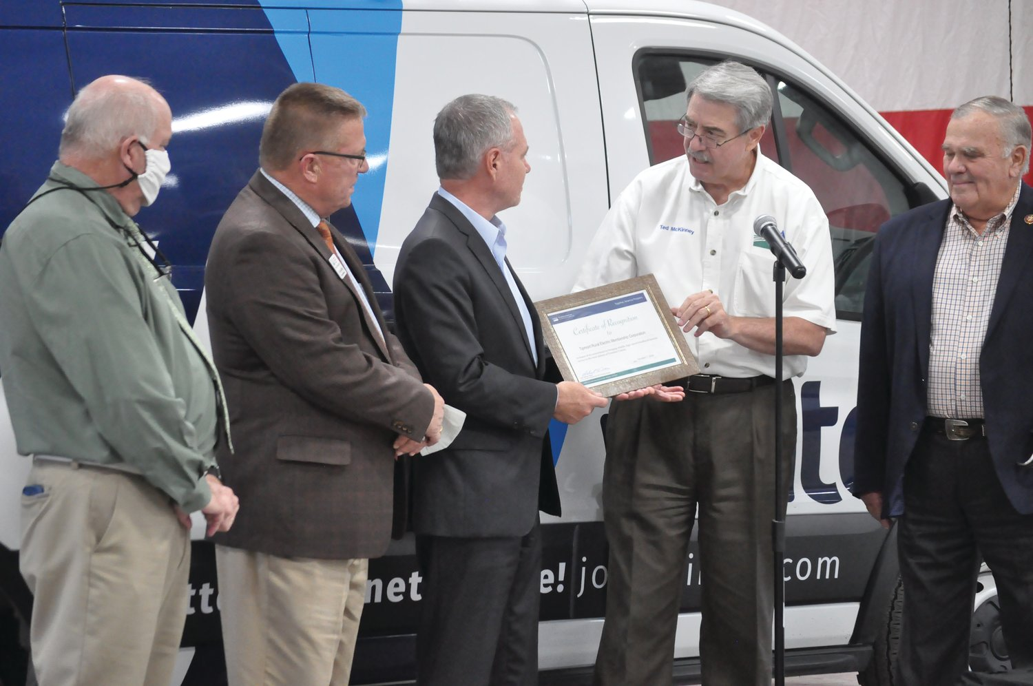 Ted McKinney, undersecretary of agriculture for trade and foreign agricultural affairs, presents a certificate of recognition to Tipmont REMC CEO Ron Holcomb as dignitaries look on Wednesday near Kingman. Tipmont/Wintek received more than $1 million in federal matching funds to expand high-speed internet to additional homes, farms and businesses in Fountain County.