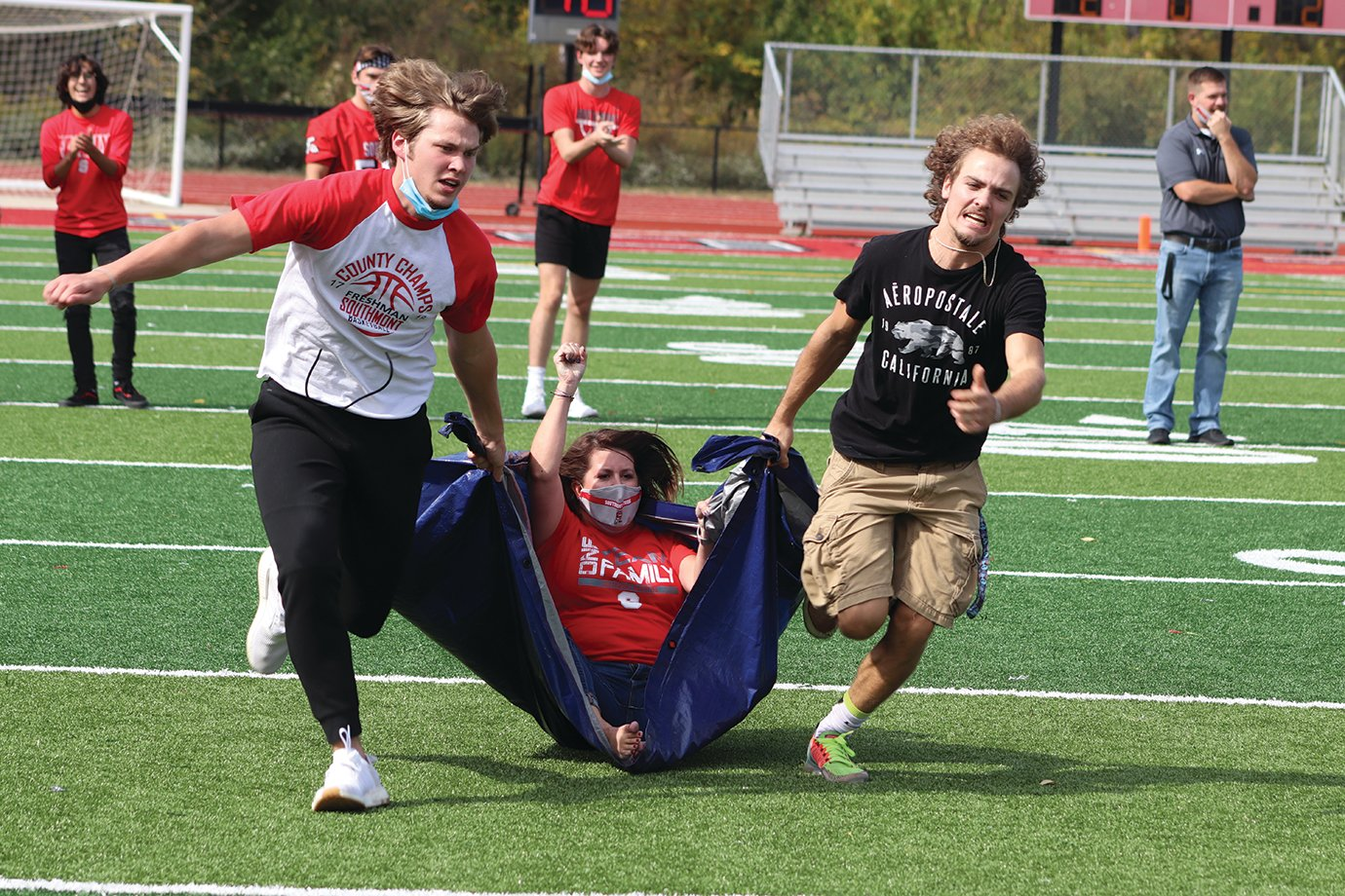 High school teacher Melissa Norman is dragged downfield by two Southmont seniors in a relay race between classes.