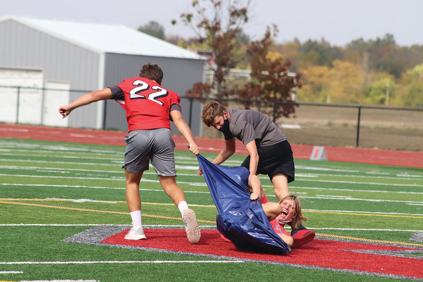 "Teacher Cindy Bannon redefines the term ""kicking and screaming"" as she is dragged across midfield Friday."