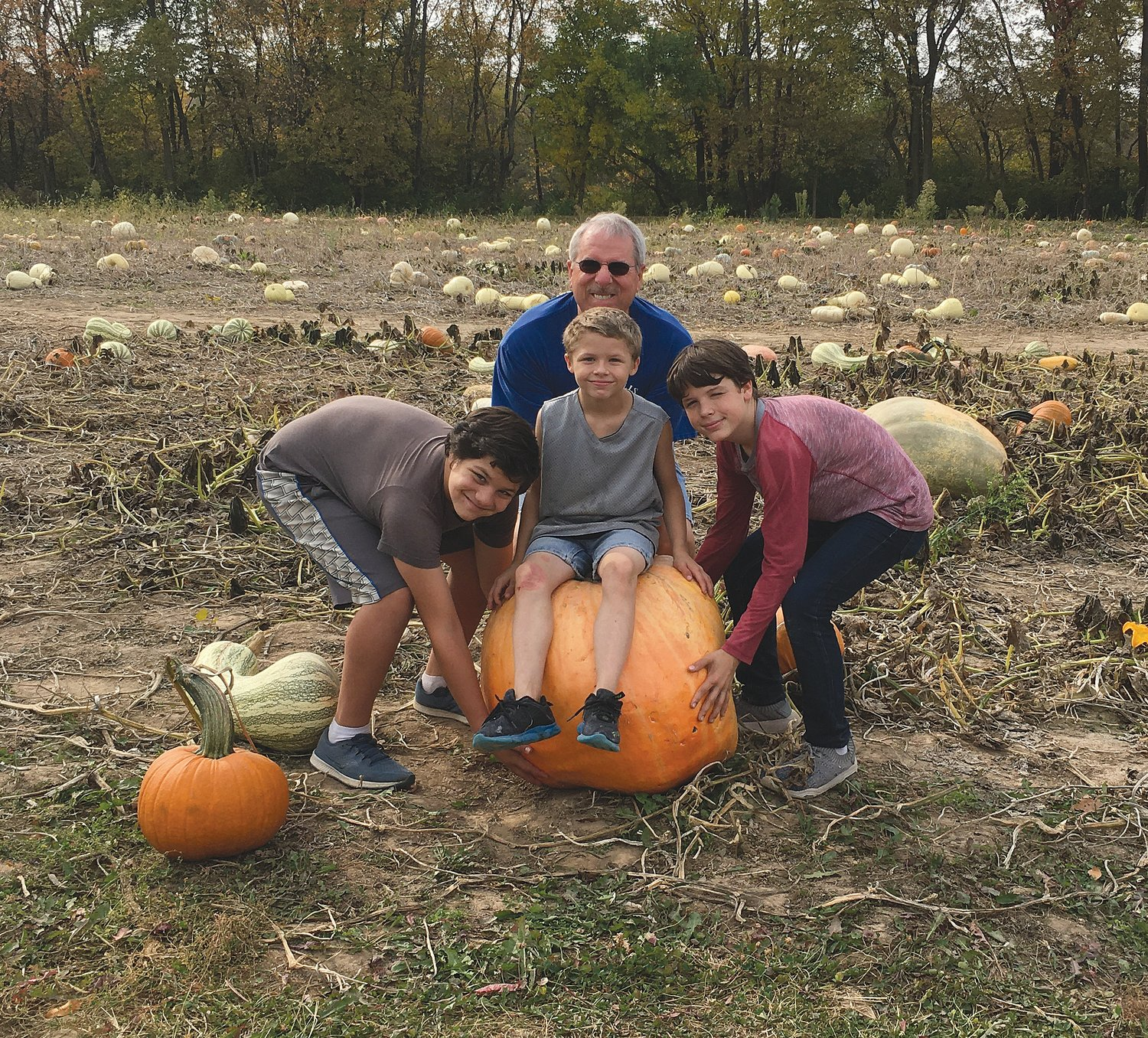 Steve Akers, Draco and brothers try to lift a pumpkin.