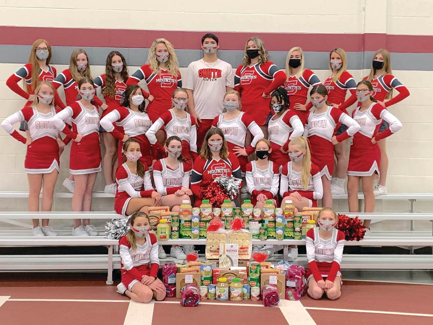 The Southmont cheerleading squad poses for a photo ahead of delivering traditional Thanksgiving meal ingredients to the organizers of the Community Thanksgiving Dinner.