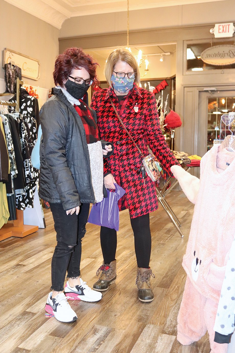 Lindsay Williamson, left, and Jennifer Lowe shop for holiday savings Saturday at Heathcliff's downtown. Many businesses and restaurants extended their hours and Black Friday deals, creating a bustling downtown for Shop Small Saturday.