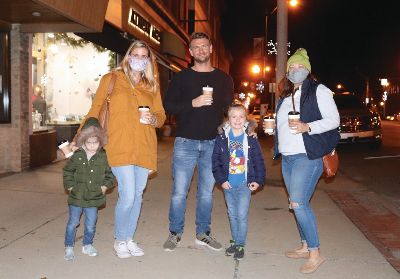 Richelle and Dan Jeffries and daughters Caytlin and Caroline enjoy hot drinks on a crisp night with friend Jamie Selby, right, downtown during Shop Small Saturday.