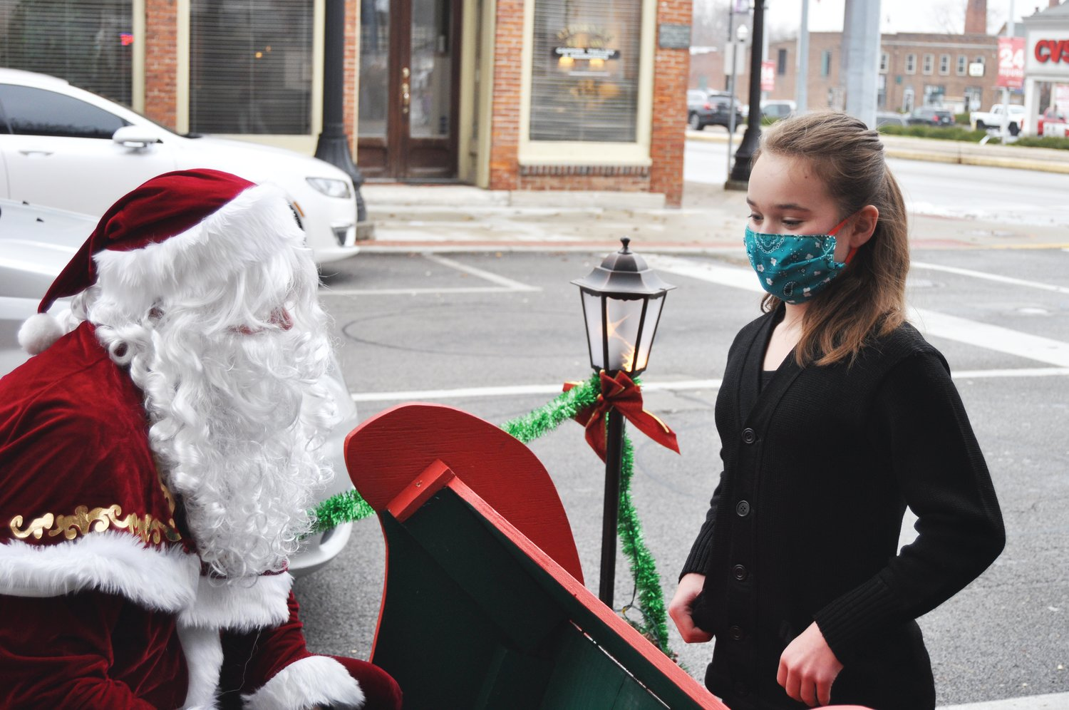 Acelyn Starcevich, 10, gives her wish list to Santa at Brothers Pizza Company on Saturday. St. Nick came to the restaurant with his elves and a reindeer to visit children, who could walk up to his sleigh or deliver their lists from the car. Children received a toy and a CD featuring music from local artists.