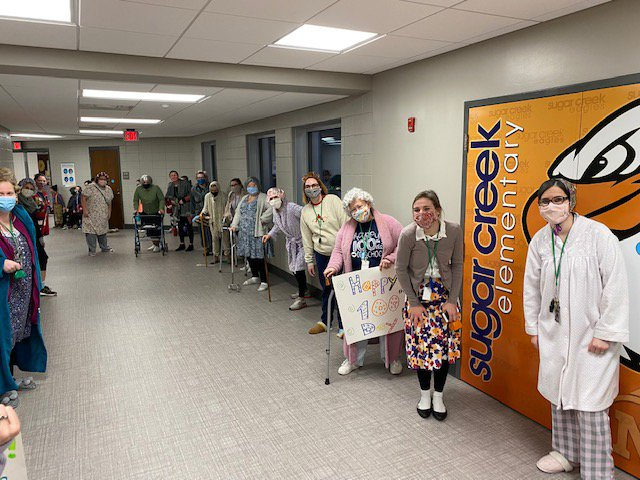 Sugar Creek Elementary School teachers lined the hallways dressed as 100-year-olds to welcome students on the 100th day of in-person school Thursday.