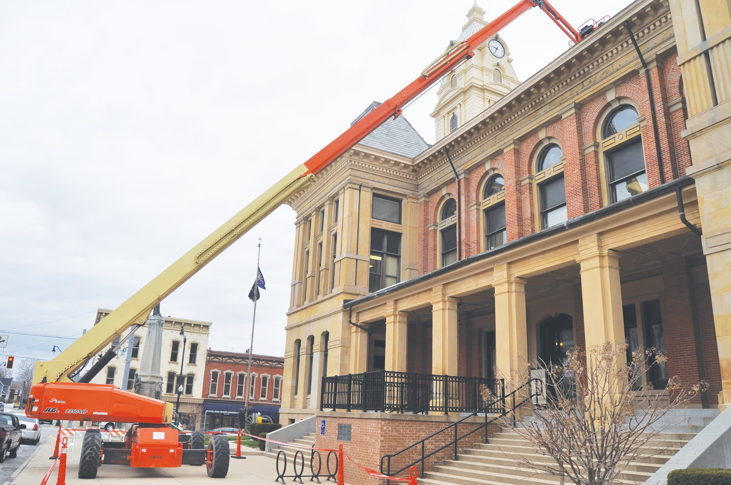 A crane touches the roof of the Montgomery County Courthouse Tuesday. Crews from South Bend-based Midland Engineering were hired to perform gutter repairs on the courthouse. The sidewalk was closed on the south side of the building during the repairs.