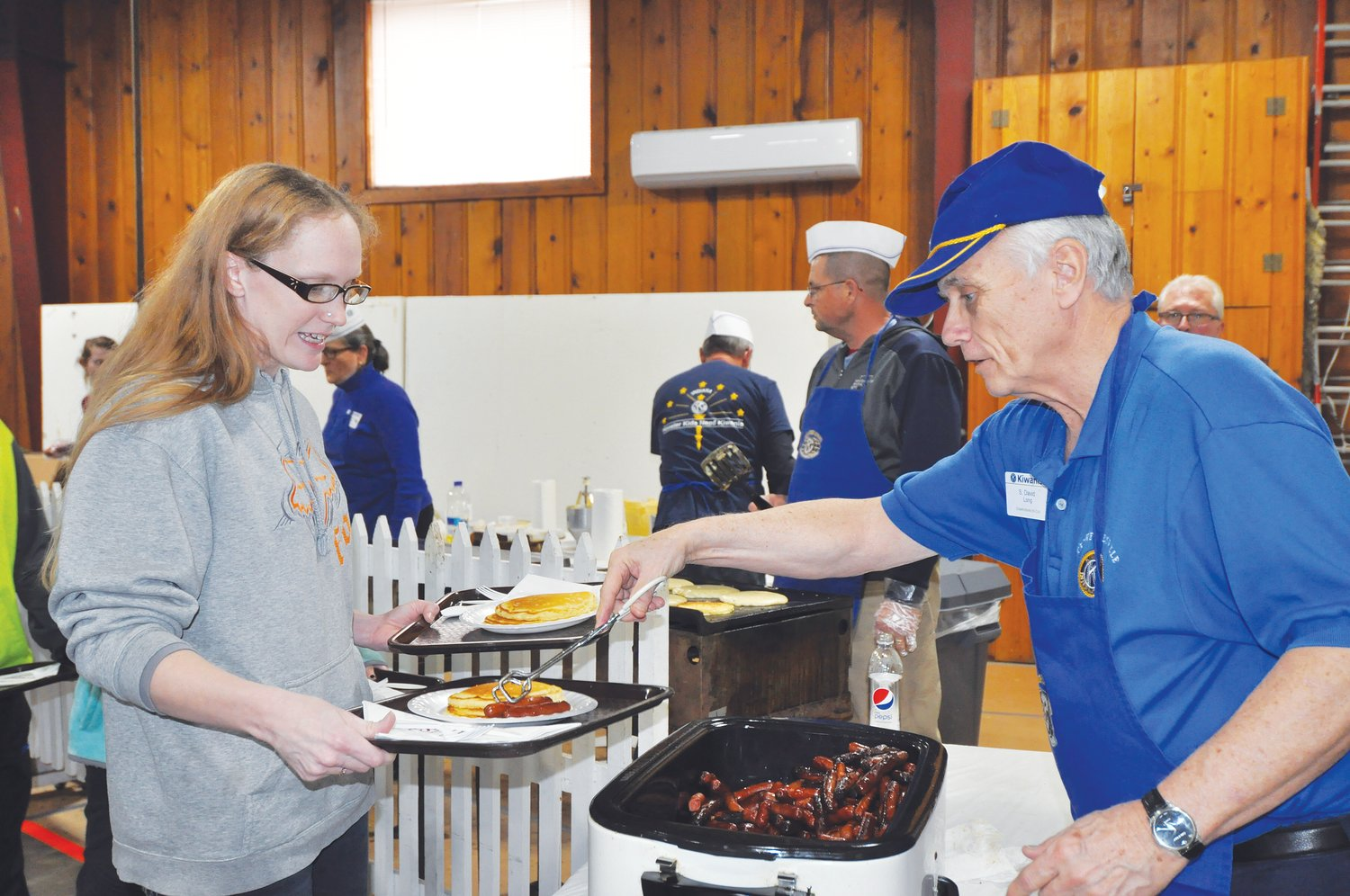 Dave Long serves sausages to Regina Lowrey at the Kiwanis Club Pancake Day at the Montgomery County 4-H Fairgrounds in 2019.  The club has partnered with Crawfordsville