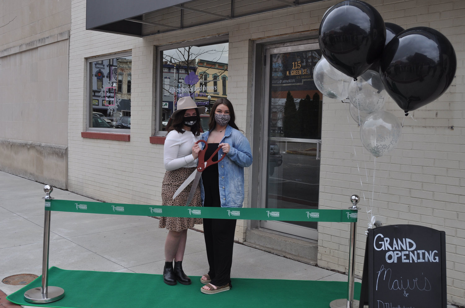 Lilly Wallace, left, and Demi Haas prepare to cut the ribbon of their businesses Maive's Boutique and djh esthetics and brows at the Weemickle Building in downtown Crawfordsville.