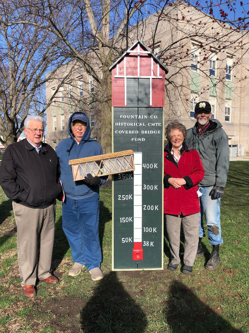 The Fountain County Historical Committee is raising funds to preserve the Cade's Mill Covered Bridge south of Covington. From left is Jim Hegg, Fountain County Art Council president; Henry Schmitt, historical committee chairman; Carol Freese, Fountain County historian; and Bob Dowell, thermometer creator.