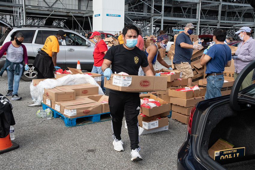 Brett Mills carries food to a car during a food bank event at Dover International Speedway on Wednesday.