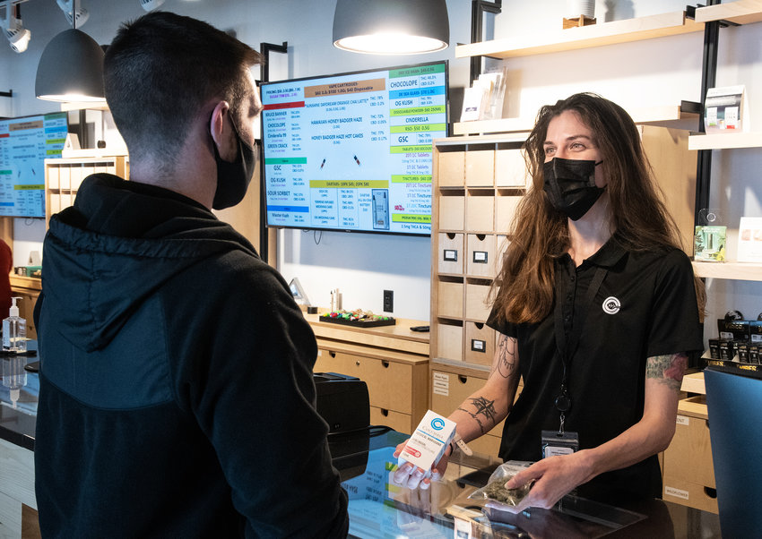 Sales Associate Grace Shinholt helps a customer at Columbia Care dispensary at the Tanger Bayside Outlets in Rehoboth Beach.