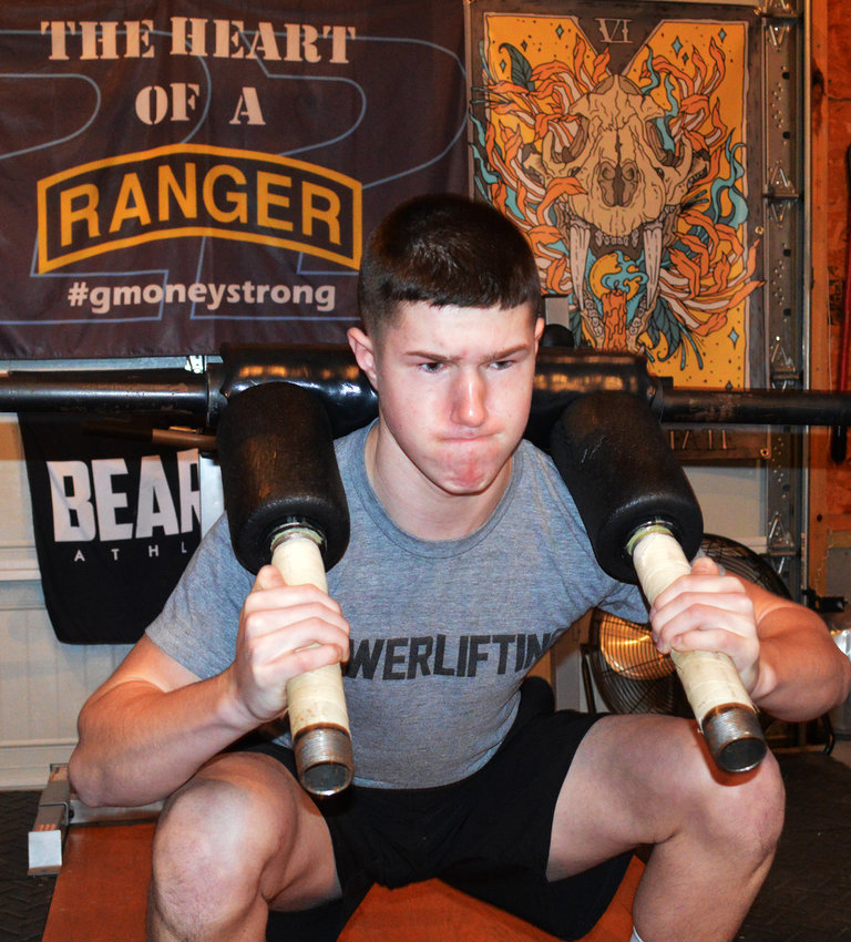 Garrett Rogers of Millsboro warms up for an evening workout at the powerlifting gym based in his family's garage in rural Millsboro. Garrett, 14, is a top-ranked lifter for his age and weight bracket, even after a tragic accident left him with brain trauma five years ago.