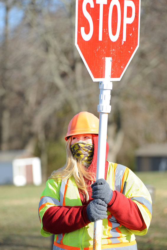Melissa Smith with DELDot  keeps her face covered from the cold wind as she works in Viola.