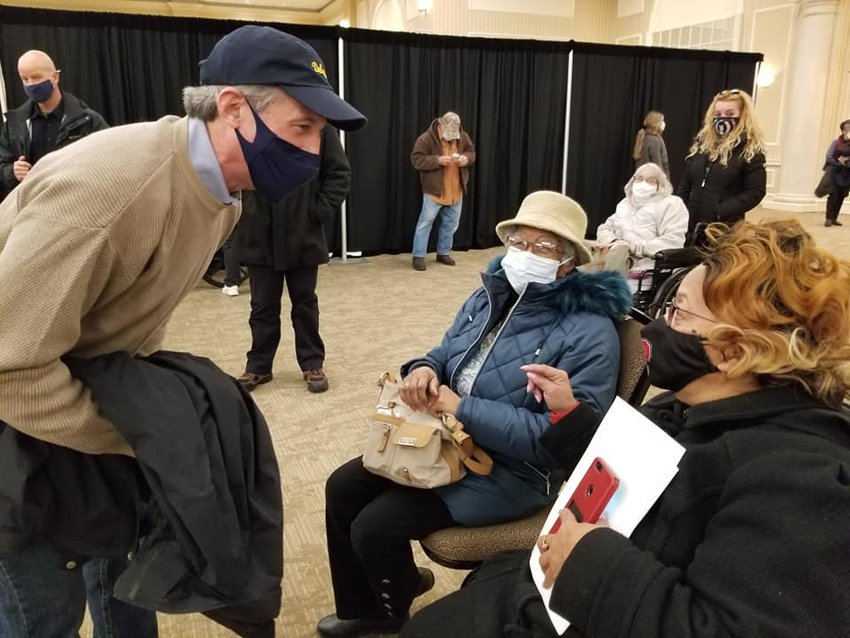Gov. John Carney greets seniors at a COVID-19 vaccination site in Wilmington earlier this year.
