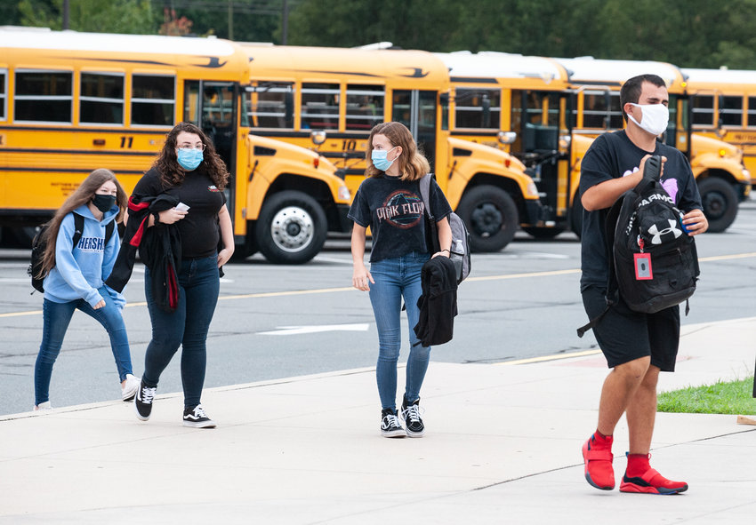 Students wearing masks and social distancing leave their buses as they start back on the first day of school at Polytech High School in September.