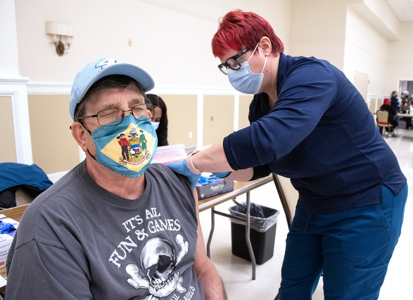 Jenny Torres gives Randy Warnick a COVID-19 vaccination at the Modern Maturity Center in Dover on Thursday.