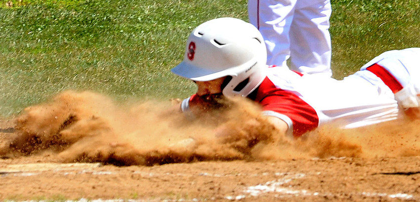 Logan Unterreiner of the Eagles plows his way across home plate to score from third on a passed ball in the first inning against Mt. Pleasant.