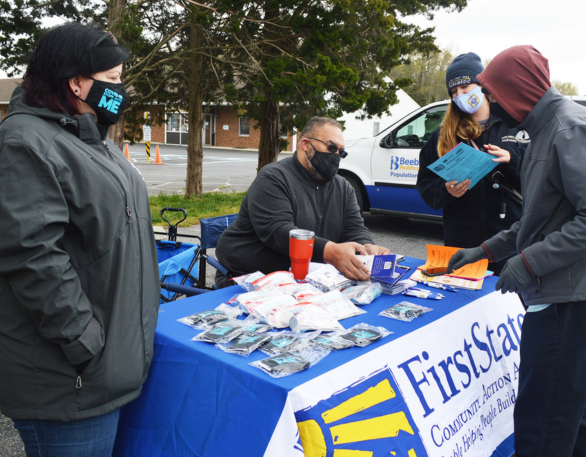 Bruce Wright of First State Community Action Agency hands out a personal protective equipment kit as an outreach component at the mobile COVID-19 vaccine clinic Tuesday at the ACE Peer Resource Center in Georgetown. At left is Jaime Sayler, FSCAA's director of community development and housing.
