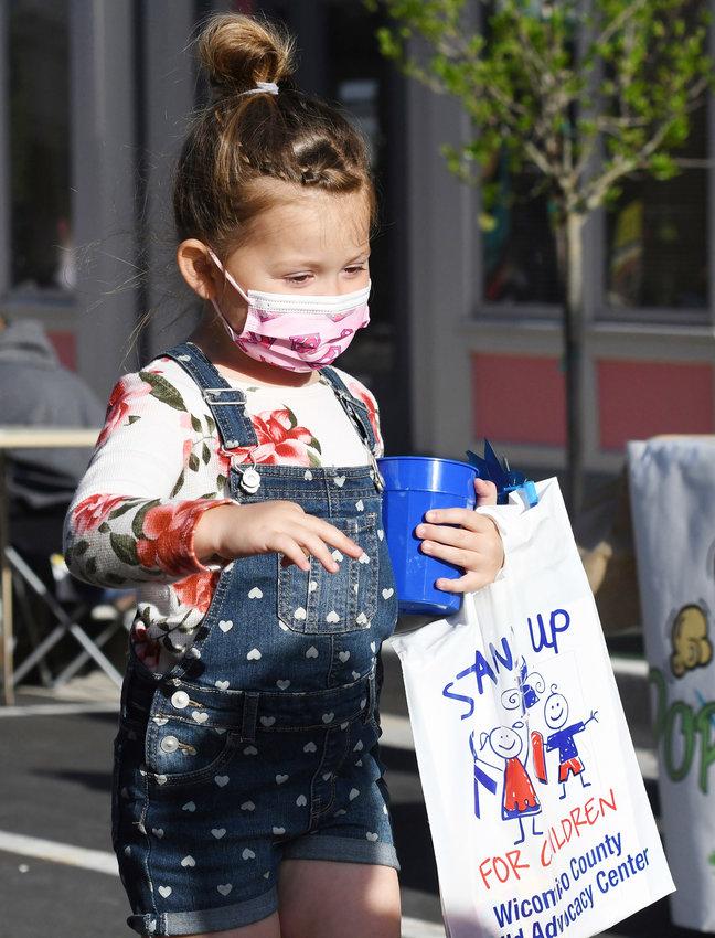 Ellie Bullis, 4, of Salisbury, carries goodies down West Main Street.