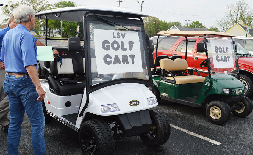 Millsboro Town Councilman Jim Kells, front, speaks with the owner of a low-speed vehicle parked next a golf cart at the Millsboro Town Center prior to Monday's Town Council meeting. Council members voted for a motion to not proceed with a charter change allowing golf carts to be driven on town-maintained roads.