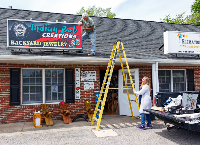 """Bob Robinson and Gail Bard install the sing of their new shop named """"Indian Bob Creations at Stover Plaza on U.S. 13."""