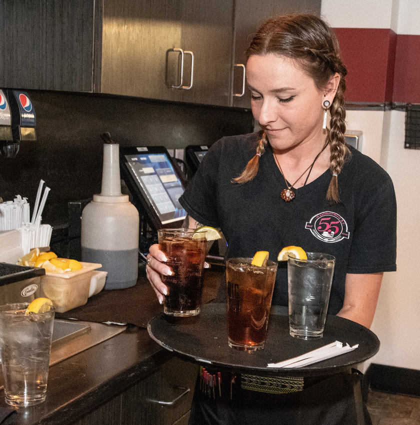 Server Katelin Rose prepares drinks at Restaurant 55 in Dover on Thursday. The eatery has around 12 employees, about a third of its number before COVID-19, and is struggling to fill its ranks.