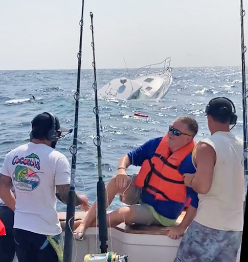"""The crew of the """"Fishbone"""" is seen rescuing victims of a sinking boat on Monday. The emergency took place during the White Marlin Open."""