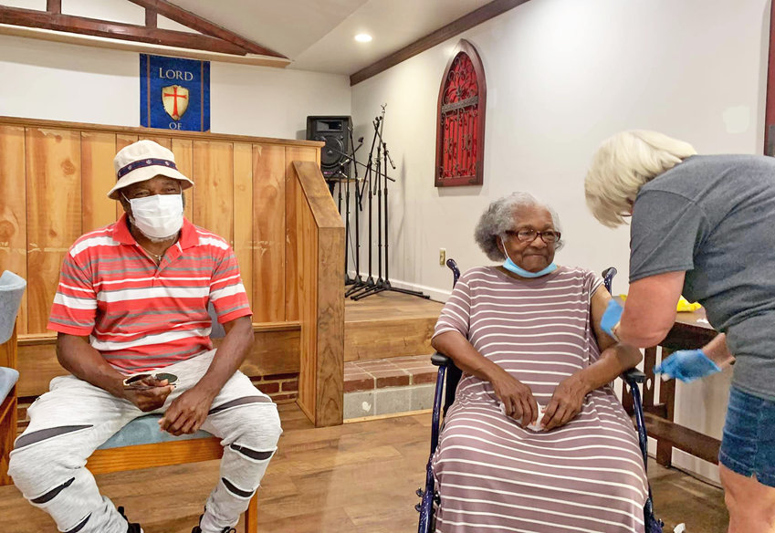 St. John's Holiness Church was the site of a recent vaccination clinic. Apostle John Cornish's mother is seen receiving a vaccine.