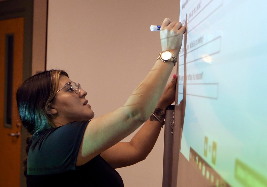 Andrea Miron of Bridgeville writes on a marker board during an English as a second language class at the Georgetown Public Library on July 22.