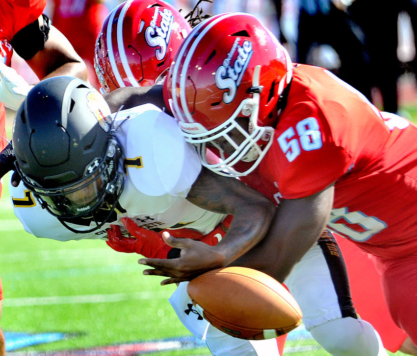 Hornet defenders Charles Peeler and Ron Holmes (58) force a fumble from Bowie quarterback Ja'Rome Johnson in the first quarter. DSU recovered the ball and a few plays later scored the first TD of the game.