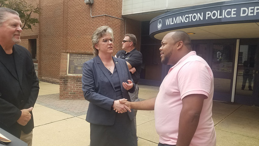 Delaware Attorney General candidate Julianne Murray shakes a hand Thursday in front of the Wilmington Police Department.