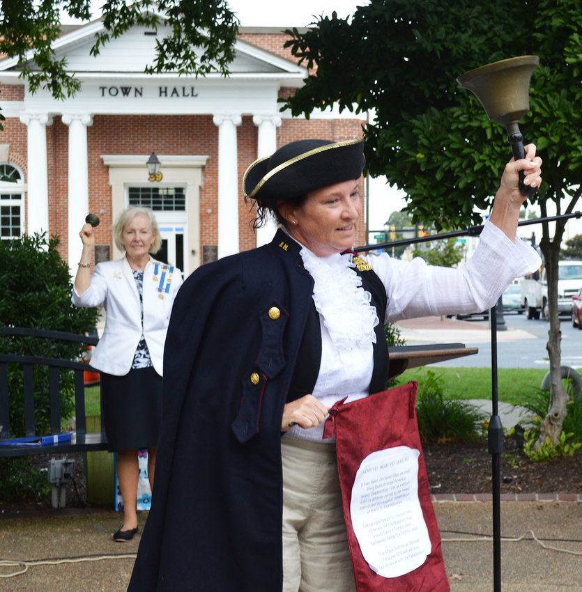 In front, Judith Schlott, chaplain for the Maj. Nathaniel Mitchell Chapter of the Daughters of the American Revolution Chapter, and, in background, Carol Evans, regent for the DAR Chapter, ring bells during the Constitution Day program on The Circle in Georgetown.