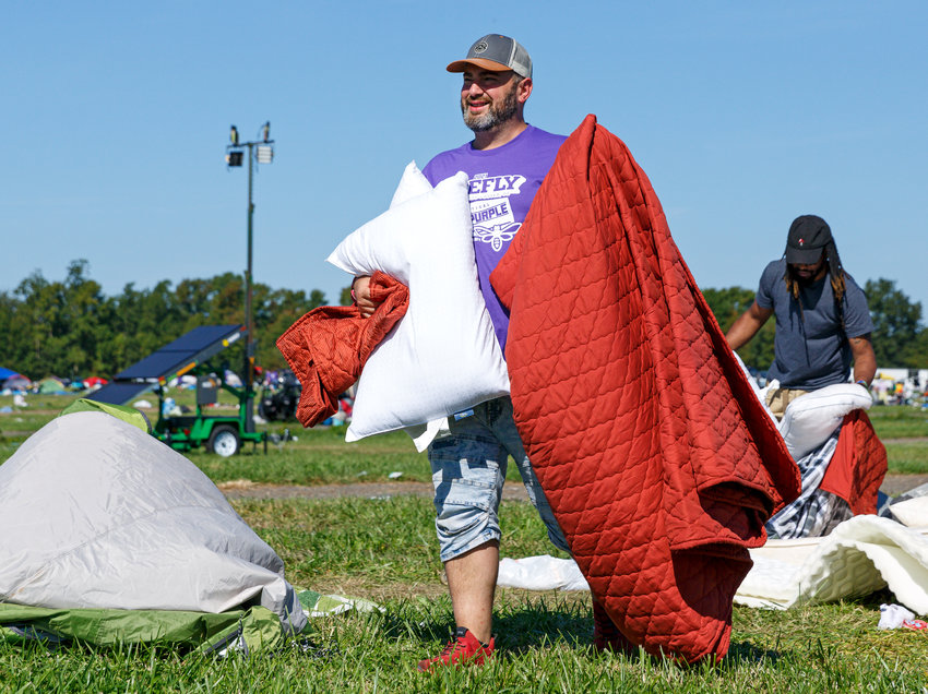 Code Purple Kent County Director Ennio Emmanuel carries blankets and pillows during a cleanup of the Firefly Music Festival campgrounds Monday. The organization hosts an event each year following the festival, to gather items to use in its initiatives for the homeless.