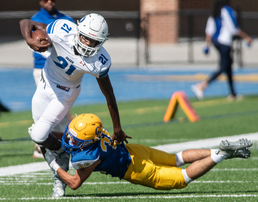 Dover's Jakwon Kilby rushes as Caesar Rodney's Julian Harris dives to make the tackle in the second quarter at CR on Saturday.